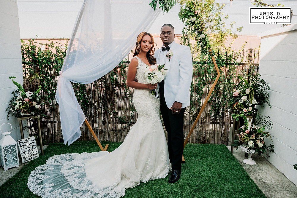 bride with lace train and groom in white tuxedo jacket posing in front of veiled and floral trellis