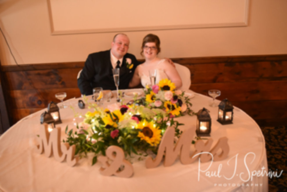 Zach & Kelly smile for a photo at their sweetheart table during their June 2018 wedding reception at Blissful Meadows Golf Club in Uxbridge, Massachusetts.