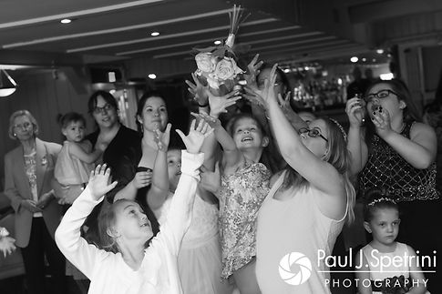 Guests battle for the bouquet during Clarissa and Jeffrey's June 2017 wedding reception at Twelve Acres in Smithfield, Rhode Island.