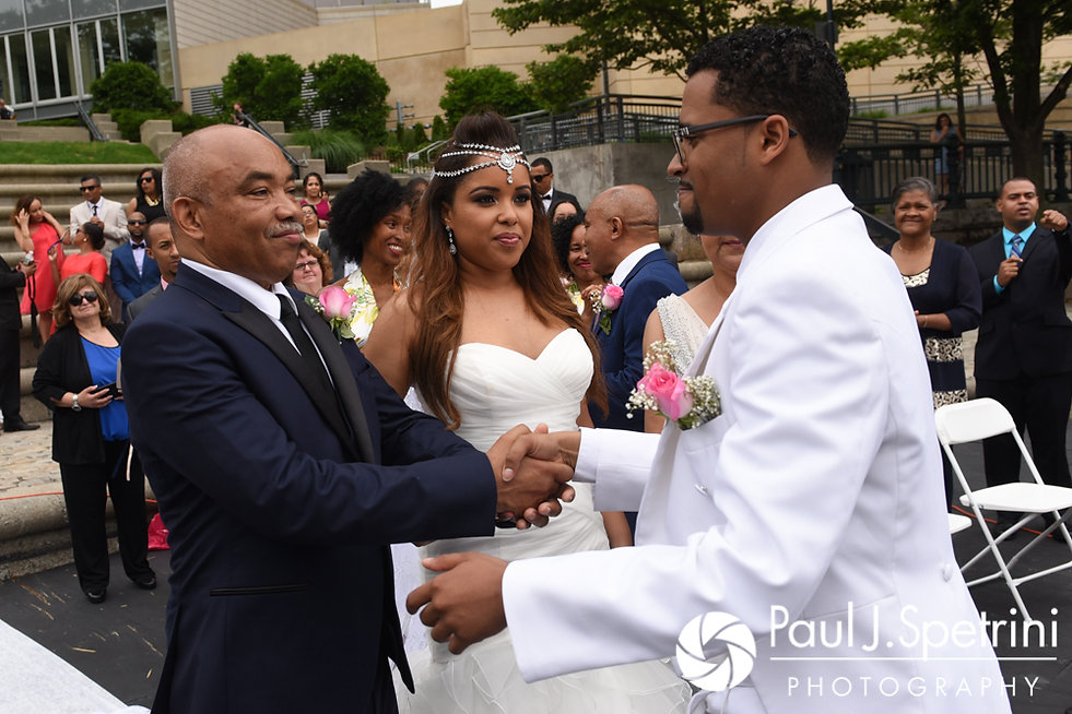 Luis shakes hands with Lucelene's father during his June 2017 wedding ceremony at Waterplace Park in Providence, Rhode Island.
