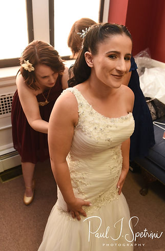 Courtnie has help zipping her dress up prior to her August 2018 wedding ceremony at Glad Tidings Church in Quincy, Massachusetts.
