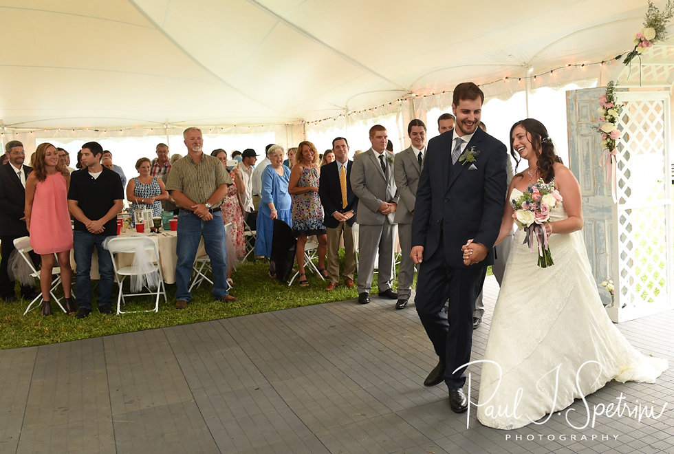 Karolyn and Ethan hold hands during their August 2018 wedding ceremony at a private residence in Sterling, Connecticut.