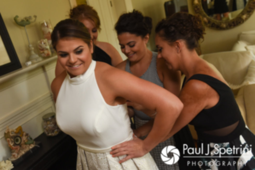 Molly has her dress zipped by her bridesmaids prior to her June 2017 wedding ceremony at Saint Romuald Chapel in Matunuck, Rhode Island.