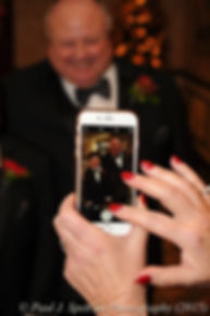 A guest takes a photo during Cathy and Ron's December 2015 wedding at Quidnessett Country Club in North Kingstown, Rhode Island.