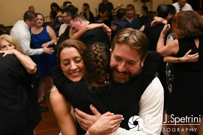 Kevin and Joanna hug a guest during their October 2017 wedding reception at Cranston Country Club in Cranston, Rhode Island.