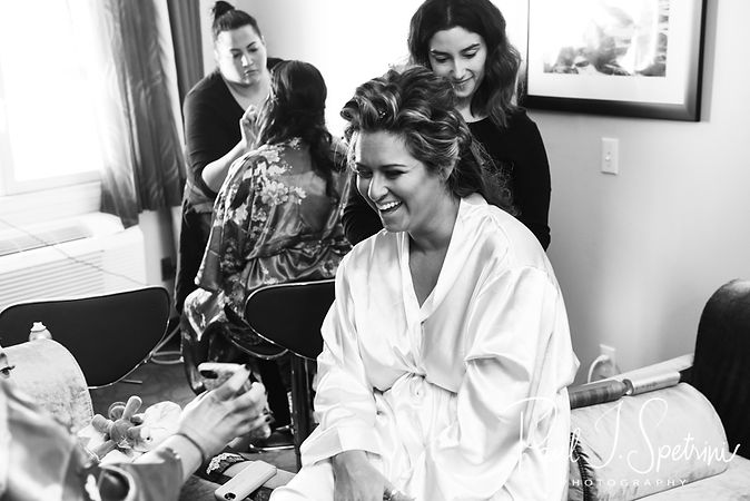 Cara laughs during her bridal prep session at the Aqua Blue Hotel in Narragansett, Rhode Island prior to her November 2018 wedding.