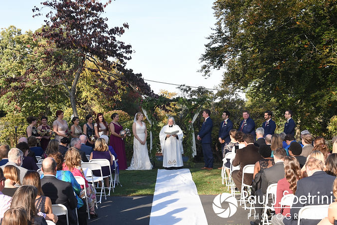 Mike and Rachel list to their officiant during their October 2017 wedding ceremony at Castle Manor Inn in Gloucester, Massachusetts.