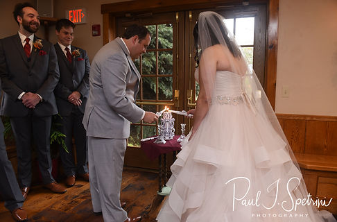 Rich and Makayla light a unity candle during their October 2018 wedding ceremony at Zukas Hilltop Barn in Spencer, Massachusetts.