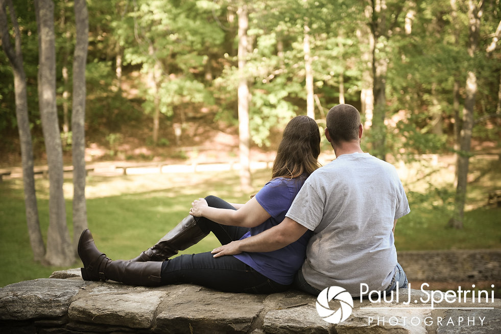 Jennifer and Kevin pose for a photo on a stone wall during their May 2017 engagement session at Gillette Castle State Park in East Haddam, Connecticut.