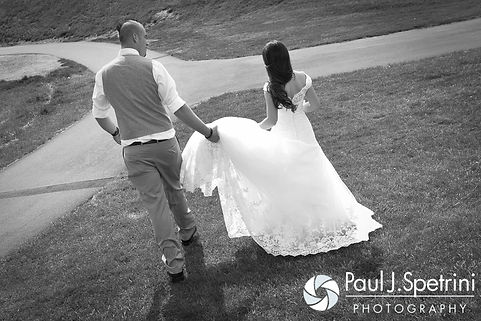 Ian helps Krystal walk in her dress following their May 2016 wedding at Colt State Park in Bristol, Rhode Island.