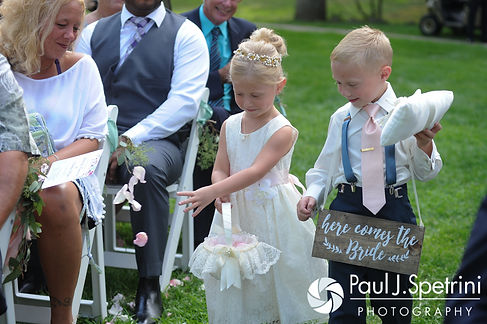 Guests watch as the flower girl and ringbearer walk down the aisle during Kim and Matt's August 2016 wedding at Whispering Pines Conference Center in West Greenwich, Rhode Island.