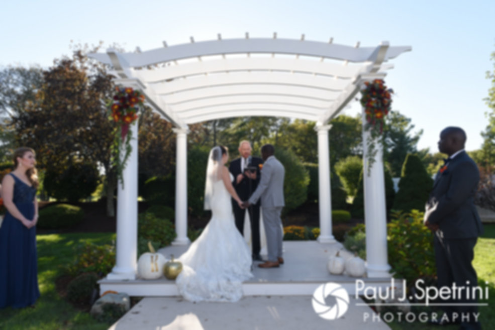 Kevin and Kristina hold hands during their October 2017 wedding ceremony at the Villa Ridder Country Club in East Bridgewater, Massachusetts.