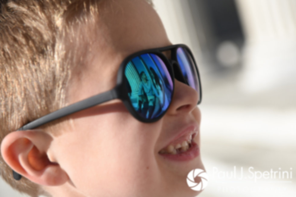Stacey's son smiles as they embrace in the reflection of his sunglasses at the Temple of Music at Roger Williams Park in Providence, Rhode Island during their May 2017 engagement shoot.
