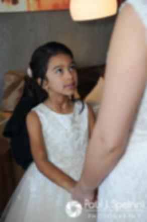 A flower girl looks up at Maria prior to her March 2016 Rhode Island wedding.