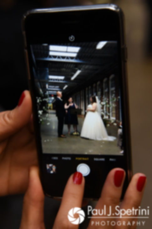 A guest takes a photo of Meridith and Matthew during their May 2017 wedding ceremony at the Hope Artiste Village in Pawtucket, Rhode Island.