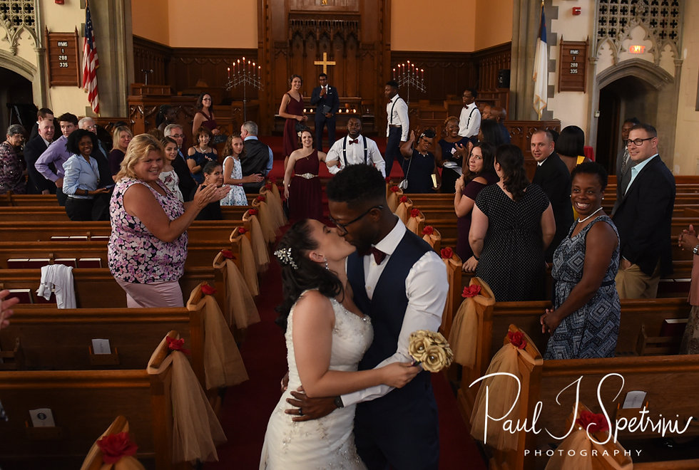 Courtnie and Richardson kiss during their August 2018 wedding ceremony at Glad Tidings Church in Quincy, Massachusetts.
