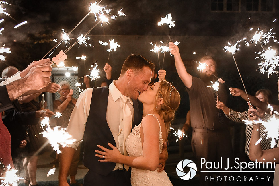 Kim and Matt kiss during a sparkler exit following their August 2016 wedding at Whispering Pines Conference Center in West Greenwich, Rhode Island.