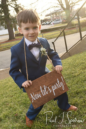 The ring bearer holds a sign following Stacey & Mack's December 2018 wedding ceremony at St. Teresa's Church in Attleboro, Massachusetts.