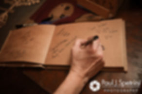 A guests signs the guestbook during Samantha and Dale's October 2017 wedding reception at the Golden Lamb Buttery in Brooklyn, Connecticut.