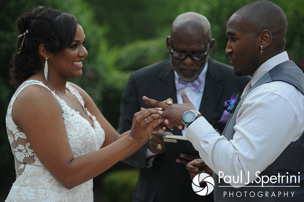 Kemi puts a ring on Warren's hand during their August 2016 wedding reception at the Villa at Riddler Country Club in East Bridgewater, Massachusetts.