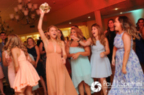 A guest catches Cassie's bouquet during her July 2017 wedding reception at Rachel's Lakeside in Dartmouth, Massachusetts.