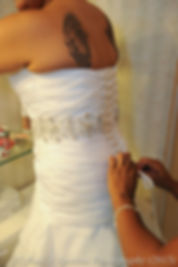 Jean Andrade gets help putting her dress on.