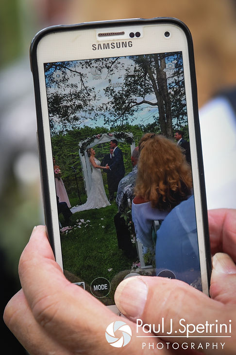 A guest takes a photo during Kim and Matt's August 2016 wedding at Whispering Pines Conference Center in West Greenwich, Rhode Island.