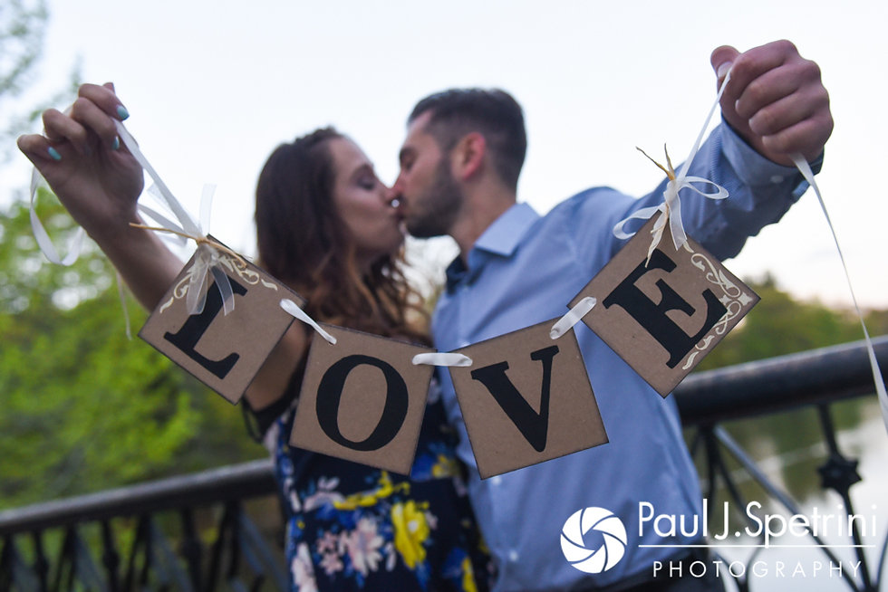 Stacey and John kiss while holding a prop on the Iron Footbridge at Roger Williams Park in Providence, Rhode Island during their May 2017 engagement shoot.