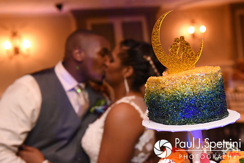 Kemi and Warren cut the cake during their August 2016 wedding reception at the Villa at Riddler Country Club in East Bridgewater, Massachusetts.