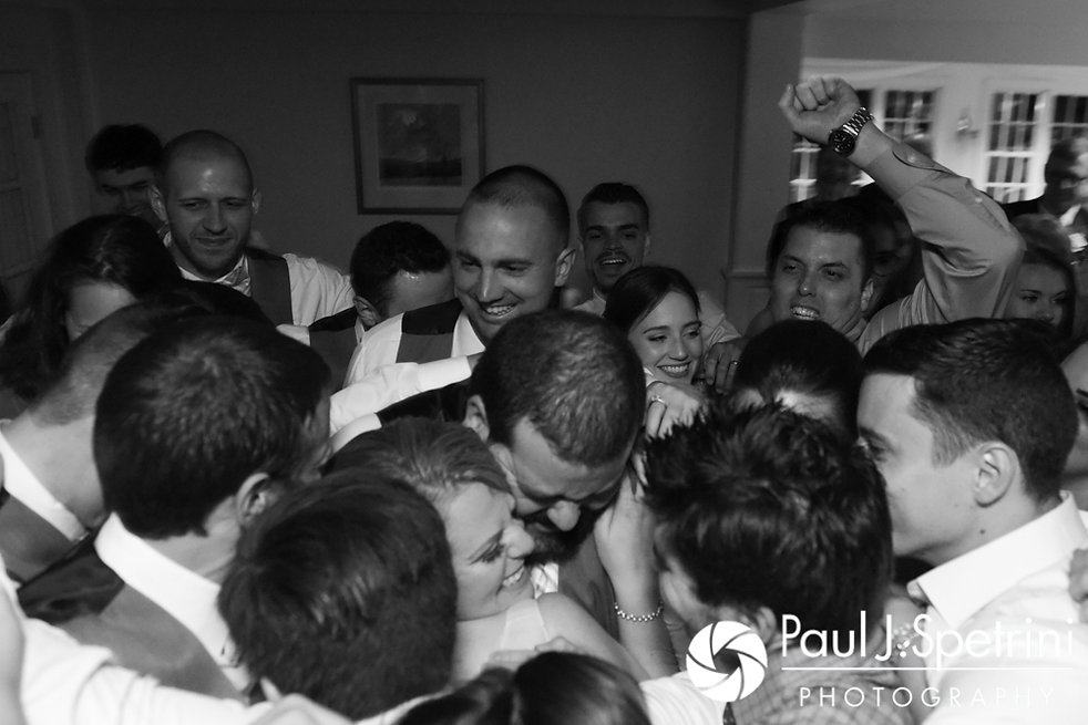 Guests swarm Melissa and Jordan for a group hug at the end of their May 2017 wedding reception at Independence Harbor in Assonet, Massachusetts.