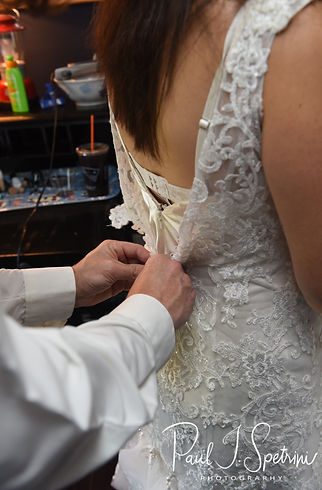 Josh helps Amanda zip up her dress prior to their October 2018 wedding reception at Loon Pond Lodge in Lakeville, Massachusetts.