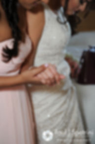 Maria holds hands with one of her bridesmaids after putting on her wedding dress prior to her March 2016 Rhode Island wedding.