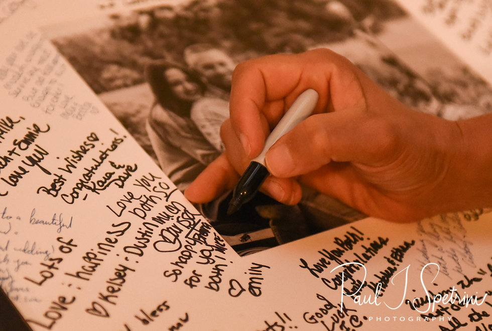 A guest signs the guestbook during Lizzy & Gabe's September 2018 wedding reception at Crystal Lake Golf Club in Mapleville, Rhode Island.