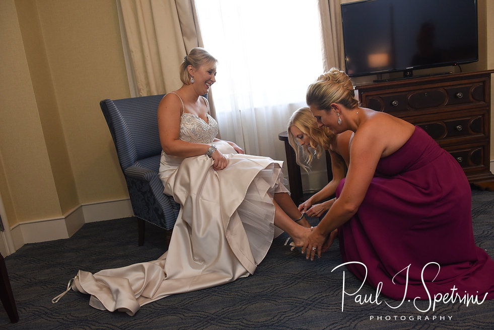 Meghan has help putting her shoes on at the Biltmore in Providence, Rhode Island prior to her September 2018 wedding ceremony at Immaculate Conception Church in Cranston, Rhode Island.