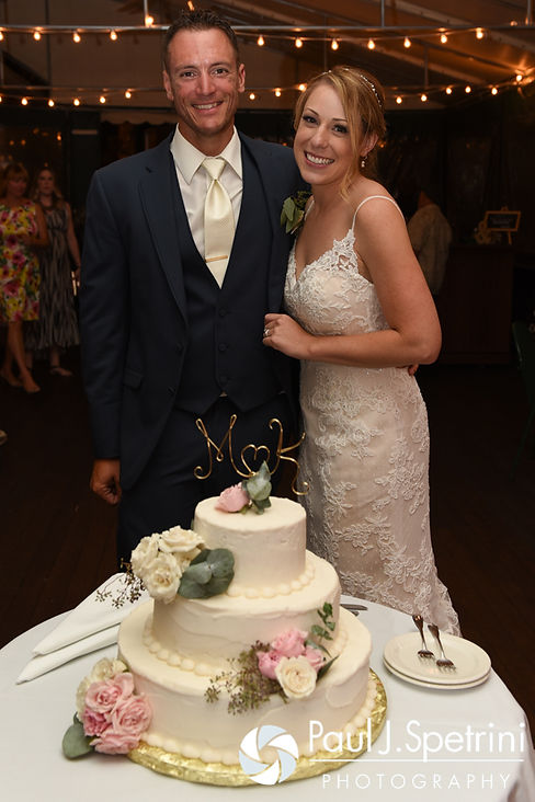 Kim and Matt get ready to cut the cake during their August 2016 wedding at Whispering Pines Conference Center in West Greenwich, Rhode Island.