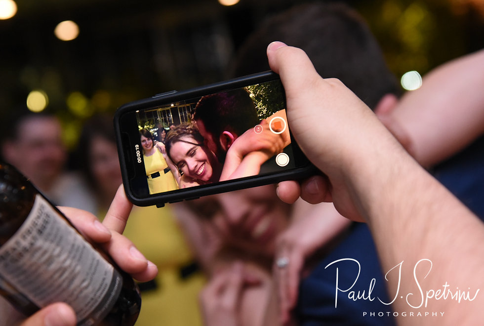 Ali & Gary are seen through a cell phone camera dancing during their May 2018 wedding reception at the Roger Williams Park Botanical Center in Providence, Rhode Island.