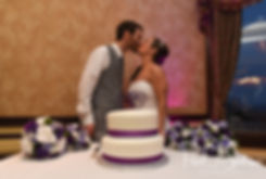 Sam and Katie kiss after cutting their cake during their April 2018 wedding reception at Quidnessett Country Club in North Kingstown, Rhode Island.