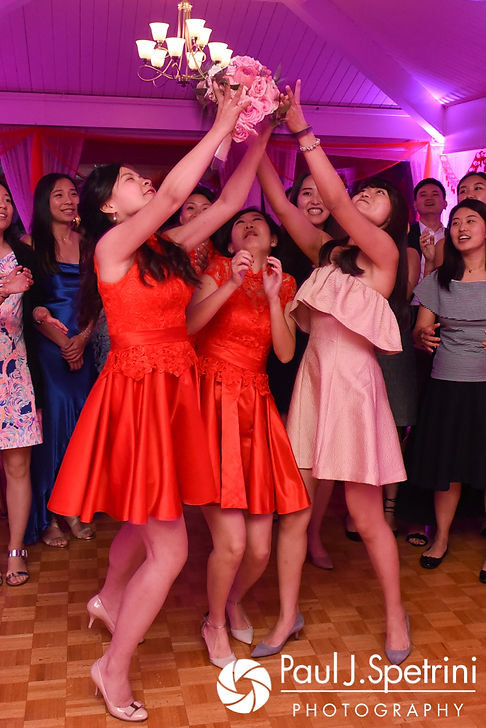 Guests vie for the bouquet during Cynthia and Ao's August 2017 wedding reception at Lake Pearl in Wrentham, Massachusetts.