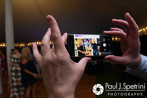 A guest takes a video during Rebecca and Kelly's August 2017 wedding reception in Warwick, Rhode Island.