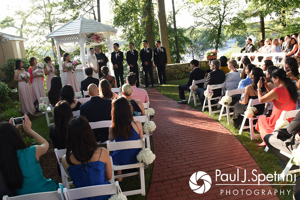 Cynthia and Ao look at their guests during their August 2017 wedding ceremony at Lake Pearl in Wrentham, Massachusetts.