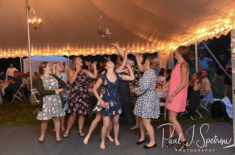 Wedding guests try to catch the bouquet during Karolyn & Ethan's August 2018 wedding reception at a private residence in Sterling, Connecticut.