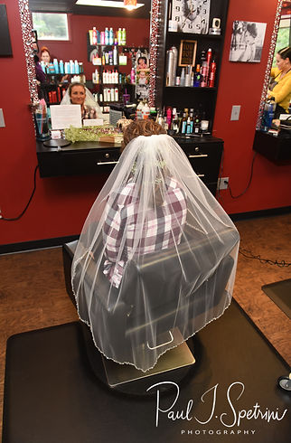 Allie looks in the mirror during her hair and makeup appointment at Per Case Salon in Smithfield, Rhode Island prior to her October 2018 wedding ceremony at South Ferry Church in Narragansett, Rhode Island.