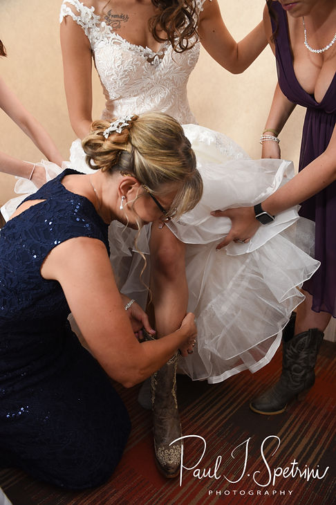 Beth has help putting her dress on prior to her August 2018 wedding ceremony at Fort Phoenix in Fairhaven, Massachusetts.