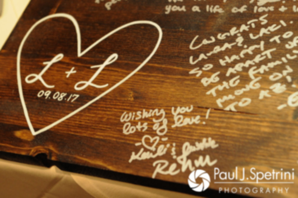A sign signed by guests is seen on display during Laura and Laki's September 2017 wedding reception at Lake of Isles Golf Club in North Stonington, Connecticut.