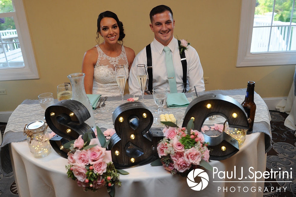 Sean and Cassie smile for a photo at their sweetheart table during their July 2017 wedding reception at Rachel's Lakeside in Dartmouth, Massachusetts.
