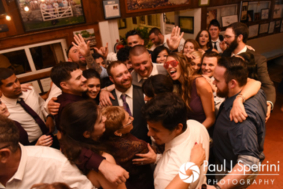 Samantha and Dale get a group hug during their October 2017 wedding reception at the Golden Lamb Buttery in Brooklyn, Connecticut.