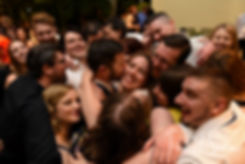 Ali & Gary smile during a group hug at the end of their May 2018 wedding reception at the Roger Williams Park Botanical Center in Providence, Rhode Island.