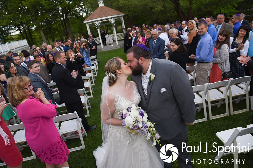 Melissa and Jordan kiss at the end of their aisle following their May 2017 wedding ceremony at Independence Harbor in Assonet, Massachusetts.
