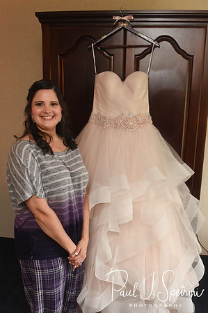 Makayla stands near her dress during her bridal prep session at Sturbridge Host Hotel and Conference Center In Sturbridge, Massachusetts prior to her October 2018 wedding.