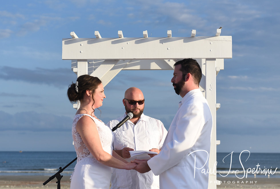 Mike and Selah hold hands during their August 2018 wedding ceremony at The Rotunda Ballroom at Easton's Beach in Newport, Rhode Island.